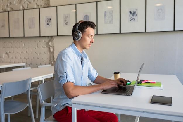 Giovane uomo fiducioso che lavora al computer portatile, seduto in ufficio di co-working, lavoro freelance, digitando in cuffia ascolto wireless