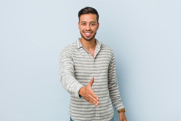 Giovane uomo filippino bello che allunga mano alla macchina fotografica nel gesto di saluto.