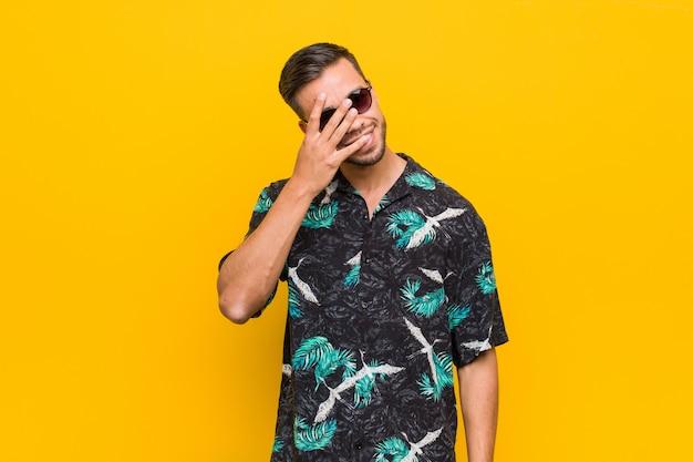 Giovane uomo filippino che indossa abiti estivi sbatte le palpebre alla macchina fotografica con le dita, imbarazzato volto che copre.