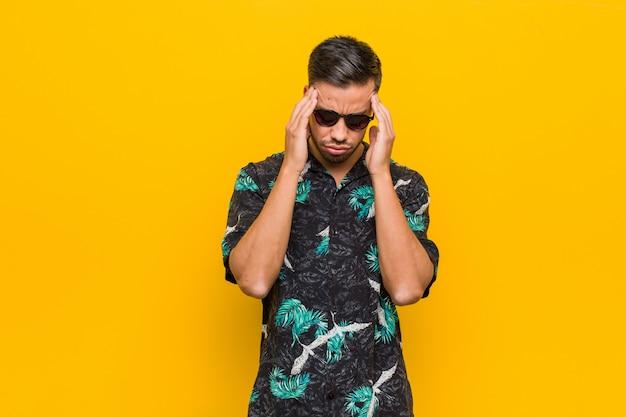 Giovane uomo filippino che indossa abiti estivi toccando le tempie e avendo mal di testa