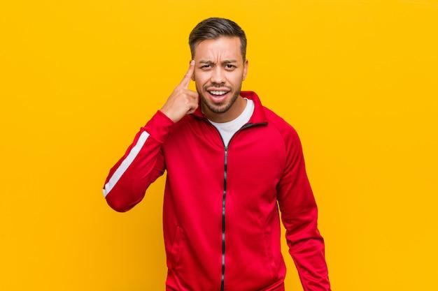 Giovane uomo filippino di forma fisica che mostra un gesto di delusione con l'indice