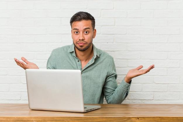 Giovane uomo filippino seduto a lavorare con il suo laptop dubitando e scrollando le spalle le spalle in gesto interrogativo