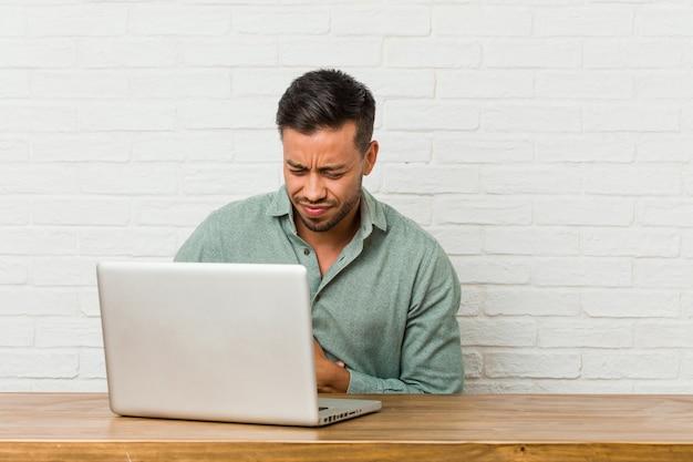 Giovane uomo filippino seduto a lavorare con il suo laptop malato, affetto da mal di stomaco