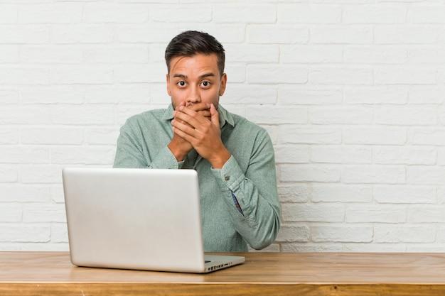 Giovane uomo filippino seduto a lavorare con il suo portatile scioccato che copre la bocca con le mani.