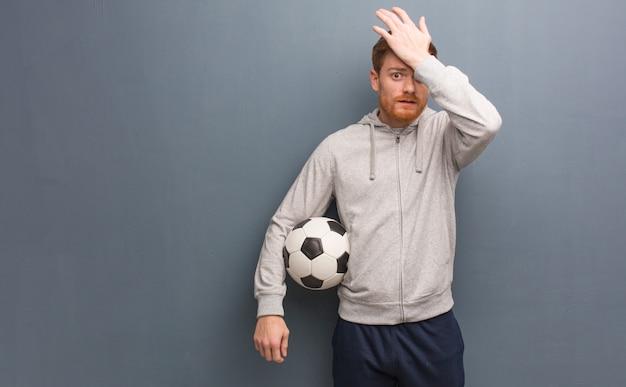 Giovane uomo fitness rossa preoccupato e sopraffatto. ha in mano un pallone da calcio.