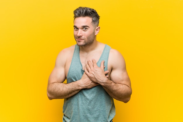 Giovane uomo fitness su uno sfondo giallo ha un'espressione amichevole, premendo il palmo al petto.
