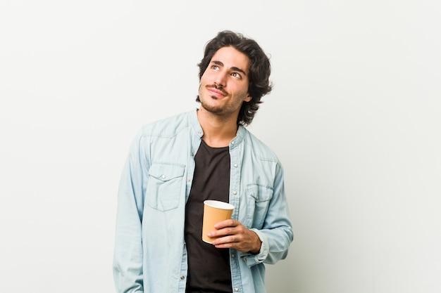 Giovane uomo freddo bere un caffè sognando di raggiungere obiettivi e scopi