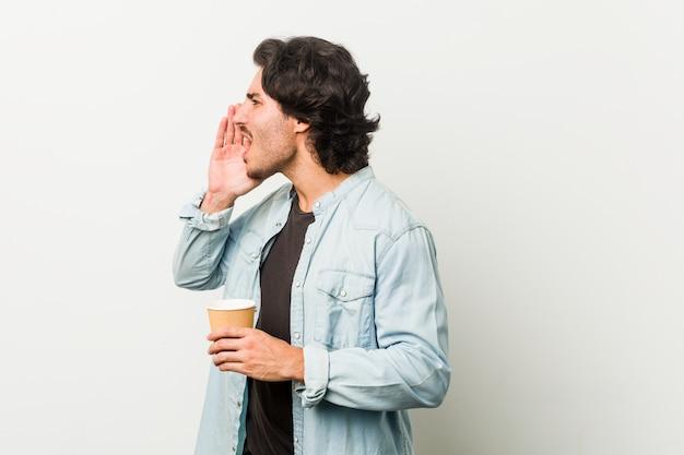 Giovane uomo freddo che beve un caffè che grida e che tiene la palma vicino alla bocca aperta.