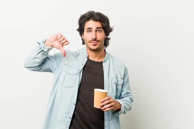 Giovane uomo freddo che beve un caffè che mostra un gesto di antipatia, pollici giù. concetto di disaccordo.