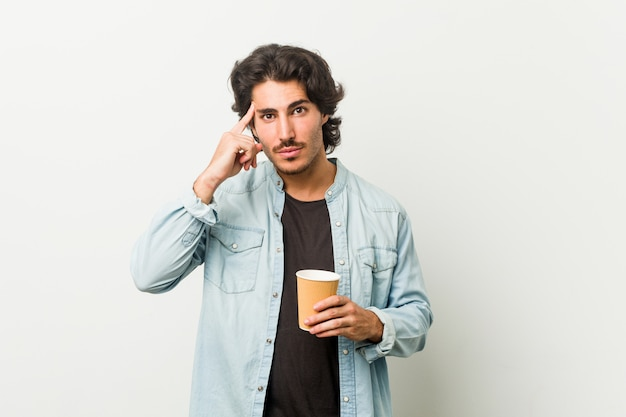 Giovane uomo freddo che beve un tempio di puntamento del caffè con il dito, pensando, incentrato su un compito.