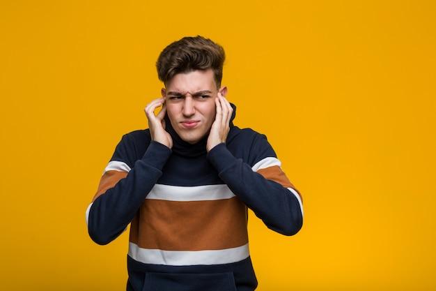 Giovane uomo freddo che indossa una felpa con cappuccio che copre le orecchie con le mani.