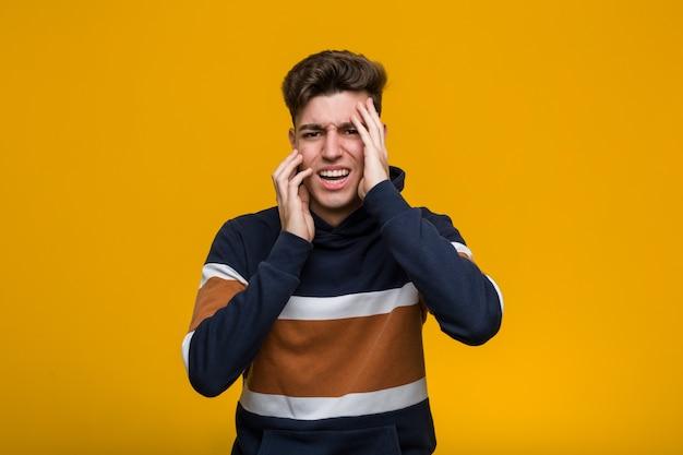 Giovane uomo freddo che indossa una felpa con cappuccio che grida e piange sconsolatamente.