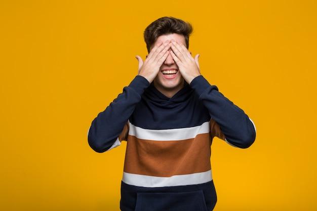 Giovane uomo freddo che indossa una felpa con cappuccio copre gli occhi con le mani, sorride ampiamente aspettando una sorpresa.