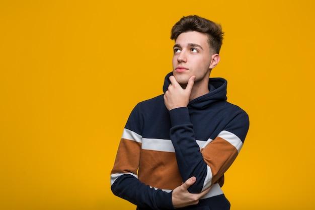 Giovane uomo freddo che indossa una felpa con cappuccio guardando lateralmente con espressione dubbiosa e scettica.