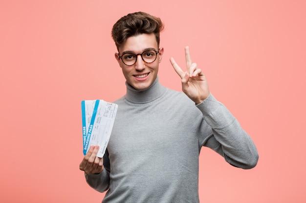 Giovane uomo freddo che tiene i biglietti aerei che mostrano il segno di vittoria e che sorridono ampiamente