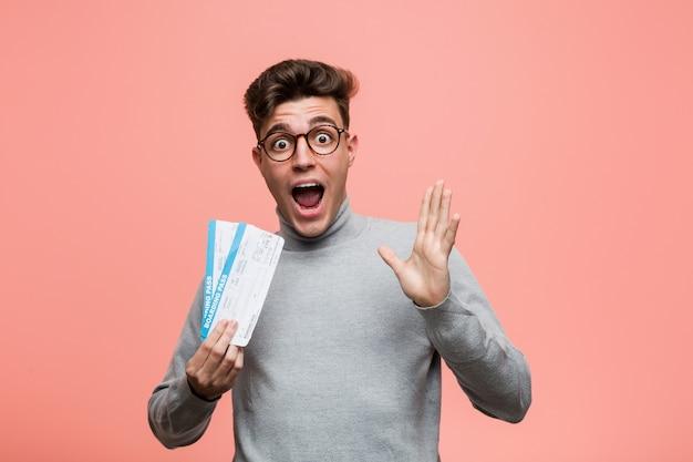 Giovane uomo freddo che tiene i biglietti aerei per celebrare una vittoria o un successo