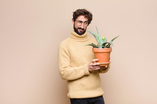 Giovane uomo freddo che tiene una pianta di cactus sopra la parete