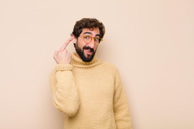 Giovane uomo freddo, confuso e perplesso, che mostra che sei pazzo, pazzo o fuori di testa contro la parete piatta