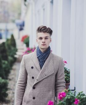 Giovane uomo freddo in cappotto sulla strada