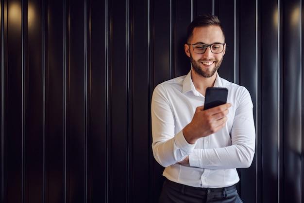 Giovane uomo geeky felice che si appoggia al muro e utilizza lo smart phone per controllare i messaggi sui social media.