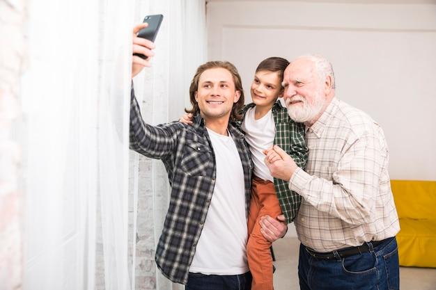 Giovane uomo gioioso prendendo selfie con la famiglia