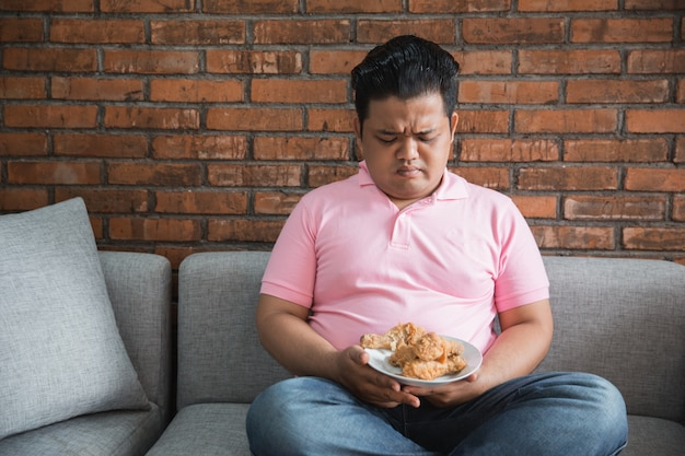 Giovane uomo grasso mangia