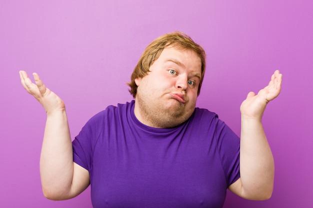 Giovane uomo grasso rosso autentico che dubita e che alza le spalle nel gesto di domanda.