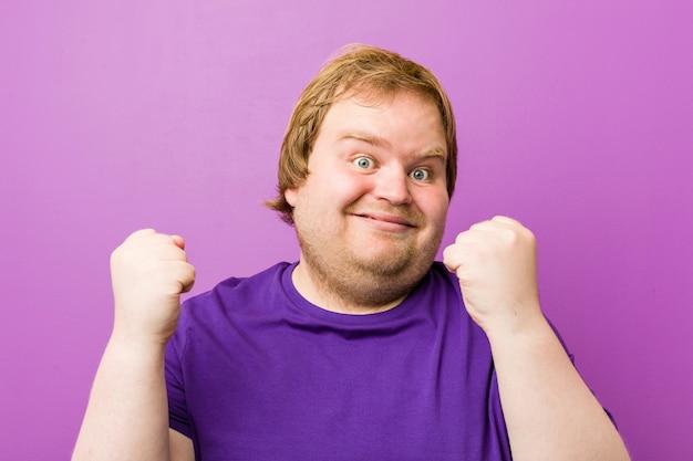 Giovane uomo grasso rosso autentico che incoraggia spensierato ed eccitato. concetto di vittoria
