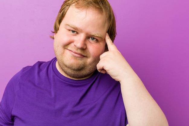 Giovane uomo grasso rosso autentico che mostra un gesto di disappunto con l'indice.