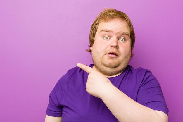 Giovane uomo grasso rosso autentico che punta al lato