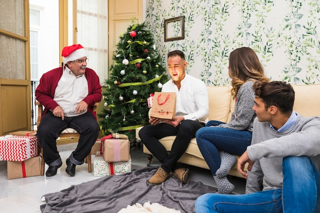 Giovane uomo guardando borsa regalo splendente
