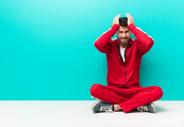Giovane uomo handosme che si sente stressato e ansioso, depresso e frustrato con un mal di testa, alzando entrambe le mani a testa contro una parete piatta