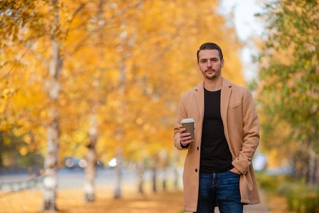Giovane uomo in autunno nel parco all'aperto