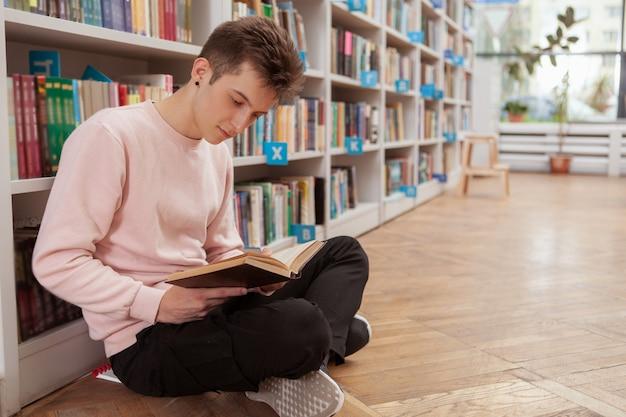 Giovane uomo in biblioteca o libreria