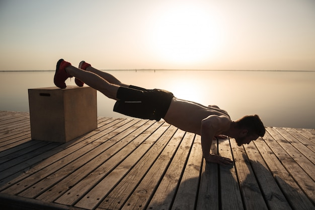 Giovane uomo in buona salute che fa i push-ups con attrezzatura speciale