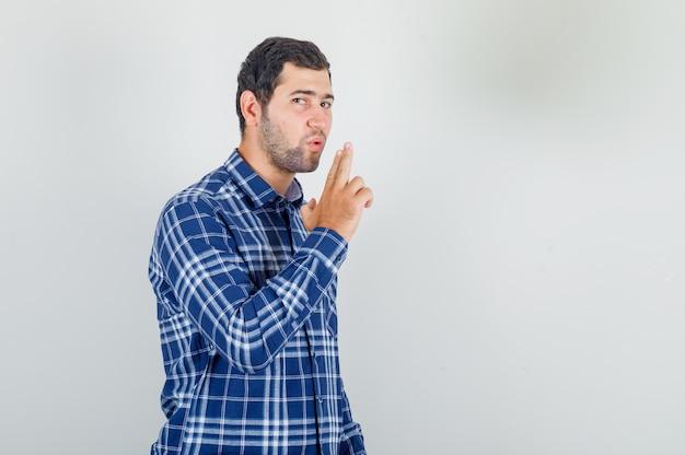Giovane uomo in camicia a quadri che soffia sulle dita che mostrano la pistola