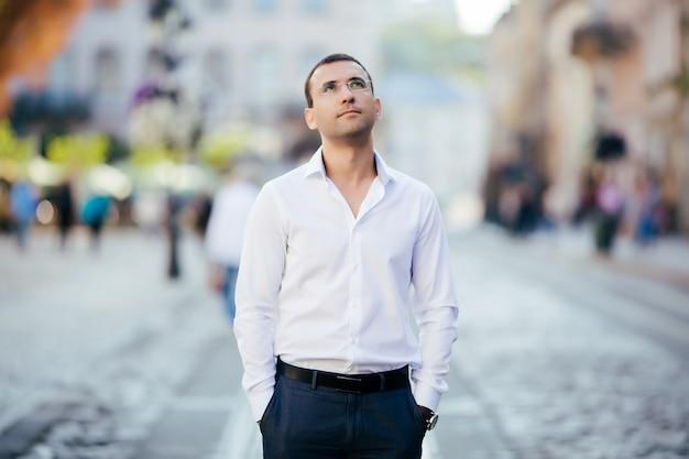 Giovane uomo in camicia e occhiali in piedi sulla strada della città