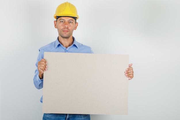 Giovane uomo in camicia, jeans, casco tenendo la tela