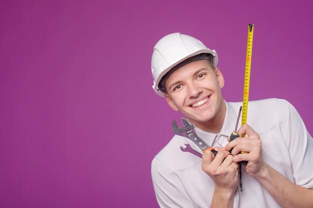 Giovane uomo in casco bianco con strumento di lavoro in mano su sfondo viola