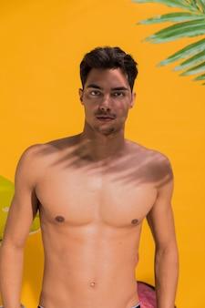 Giovane uomo in costume da bagno sulla spiaggia