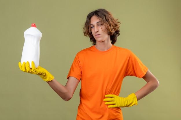 Giovane uomo in maglietta arancione che indossa guanti di gomma che mostra una bottiglia di prodotti per la pulizia guardando la fotocamera con un sorriso fiducioso in piedi su sfondo verde