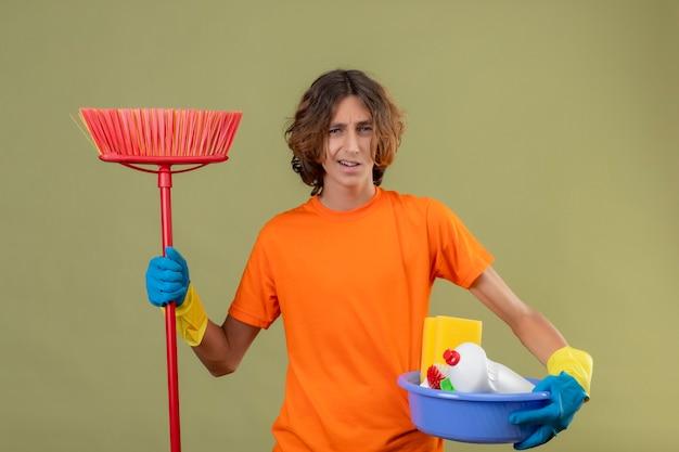 Giovane uomo in maglietta arancione che indossa guanti di gomma che tiene bacino con strumenti di pulizia e mop guardando la telecamera confuso e incerto in piedi su sfondo verde