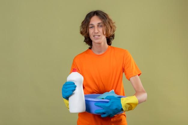 Giovane uomo in maglietta arancione che indossa guanti di gomma che tiene bacino con strumenti di pulizia e una bottiglia di prodotti per la pulizia guardando la fotocamera con un sorriso amichevole in piedi su sfondo verde