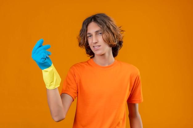 Giovane uomo in maglietta arancione che indossa guanti di gomma gesticolando con la mano facendo soldi gesto guardando la fotocamera con un sorriso fiducioso in piedi su sfondo giallo