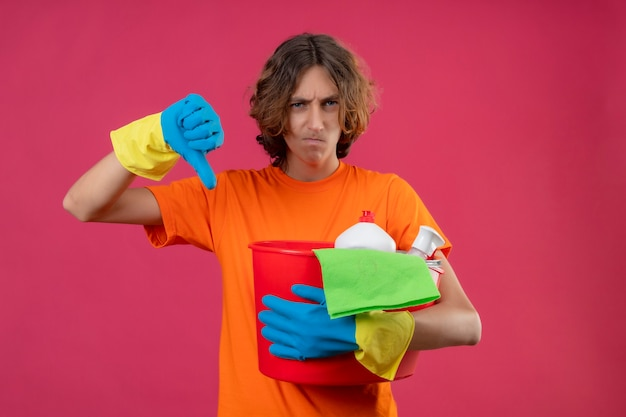 Giovane uomo in maglietta arancione che indossa guanti di gomma tenendo la benna con strumenti di pulizia cercando dispiaciuto che mostra i pollici verso il basso con la faccia accigliata in piedi su sfondo rosa
