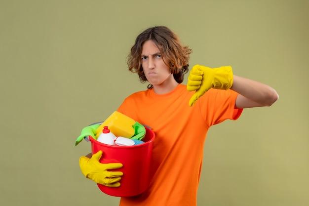 Giovane uomo in maglietta arancione che indossa guanti di gomma tenendo la benna con strumenti di pulizia guardando la telecamera scontento che mostra i pollici verso il basso con la faccia accigliata in piedi su sfondo verde
