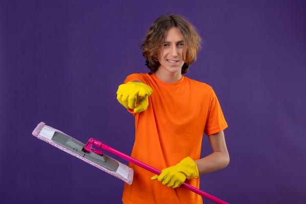 Giovane uomo in maglietta arancione che indossa guanti di gomma tenendo mop che punta alla telecamera con il sorriso sul viso positivo e felice in piedi su sfondo viola