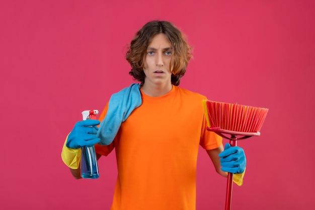 Giovane uomo in maglietta arancione che indossa guanti di gomma tenendo mop e spray per la pulizia guardando la telecamera nervoso e ansioso in piedi su sfondo rosa