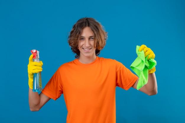 Giovane uomo in maglietta arancione che indossa guanti di gomma tenendo spray per la pulizia e rug guardando la telecamera con un sorriso fiducioso pronto per pulire in piedi su sfondo blu
