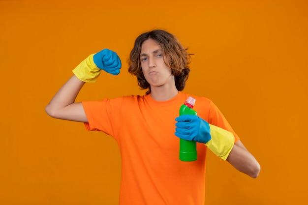 Giovane uomo in maglietta arancione che indossa guanti di gomma tenendo una bottiglia di prodotti per la pulizia stringendo il pugno rallegrandosi del suo successo e della vittoria cercando fiducioso soddisfatto di sé e orgoglioso in piedi ov